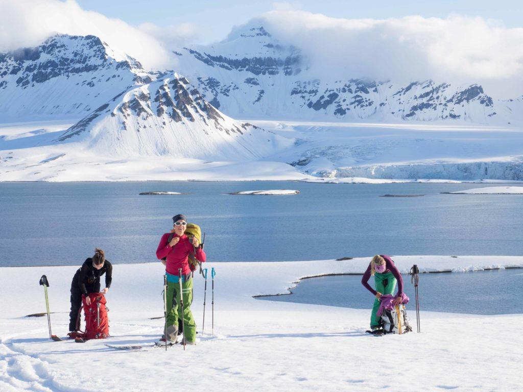 Tre venner på tur utenfor Longyearbyen på Svalbard med topptur ski på beina