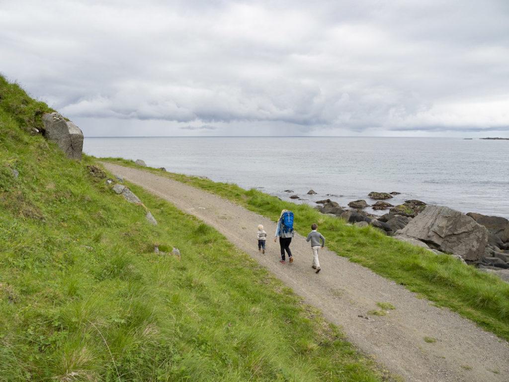 Voksen som går tur med barna i Lofoten mellom Uttakleiv og Haukland