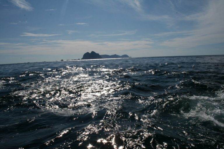Through the maelstrom to the caves. The island of Mosken right ahead, and Værøy further behind © Aqua Lofoten Coast Adventure AS