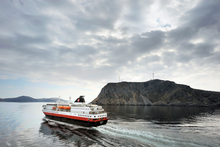 The Hurtigruten sailing past the Havøygavlen cliffside before calling at Havøysund. The photo is taken from the south bound ship when meeting the north bound ship just south of Havøysund © Jarle Wæhler/Statens vegvesen