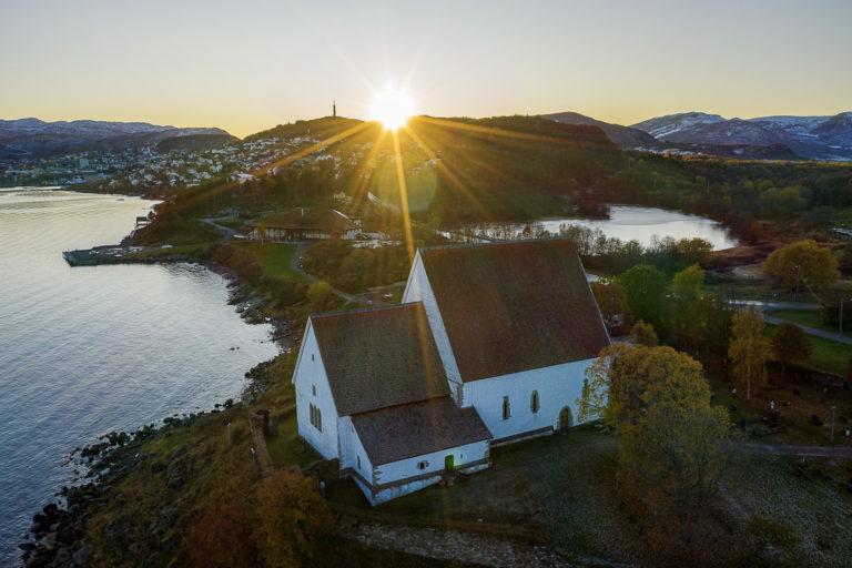Trondenes kirke i lav høstsol, Trondenes historiske senter og vatnet Laugen © Jan Schmitt