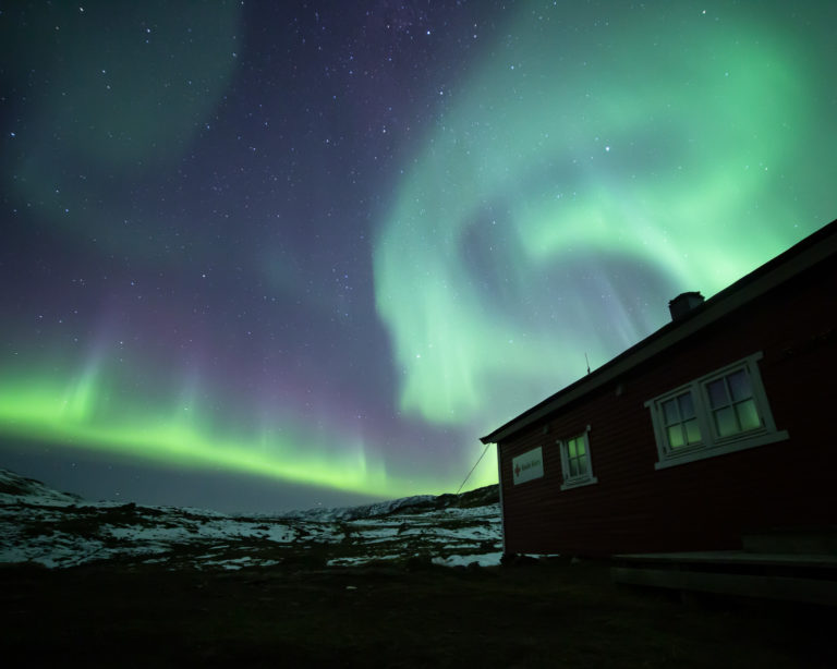 The northern lights dancing to the south of the cabins © William Copeland