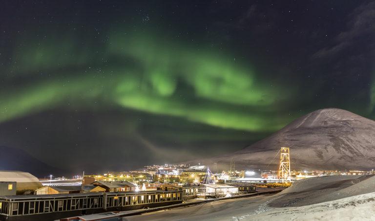 Nordlyset danser over Longyearbyen. Tårnet til høyre tilhører den gamle taubanen til gruvene © Sophie Cordon