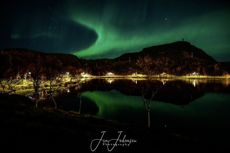 Northern Lights seen over Mount Tyven, with Lake Storvatnet in the foreground © Jim Johansen