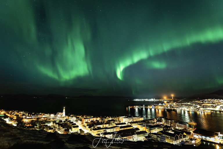 Northern Lights seen from Mount Salen The church steeple is in the middle, and the island of Sørøya is afar © Jim Johansen