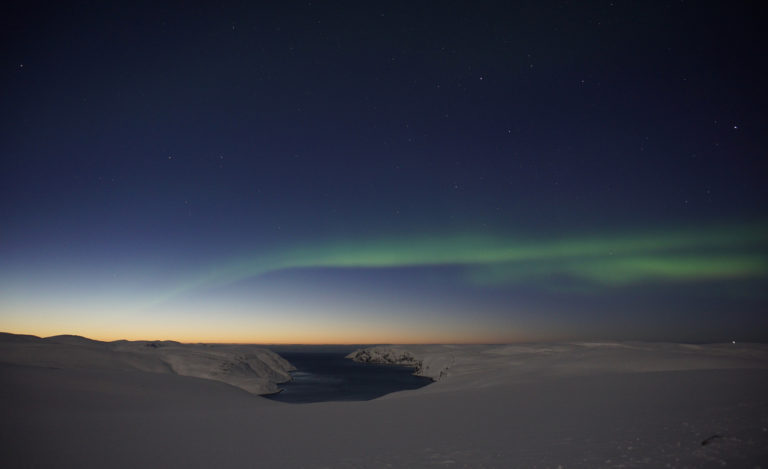 The sun has set in the west, and the Northern Lights are starting to appear over the Tufjord ©www.71-nord.no