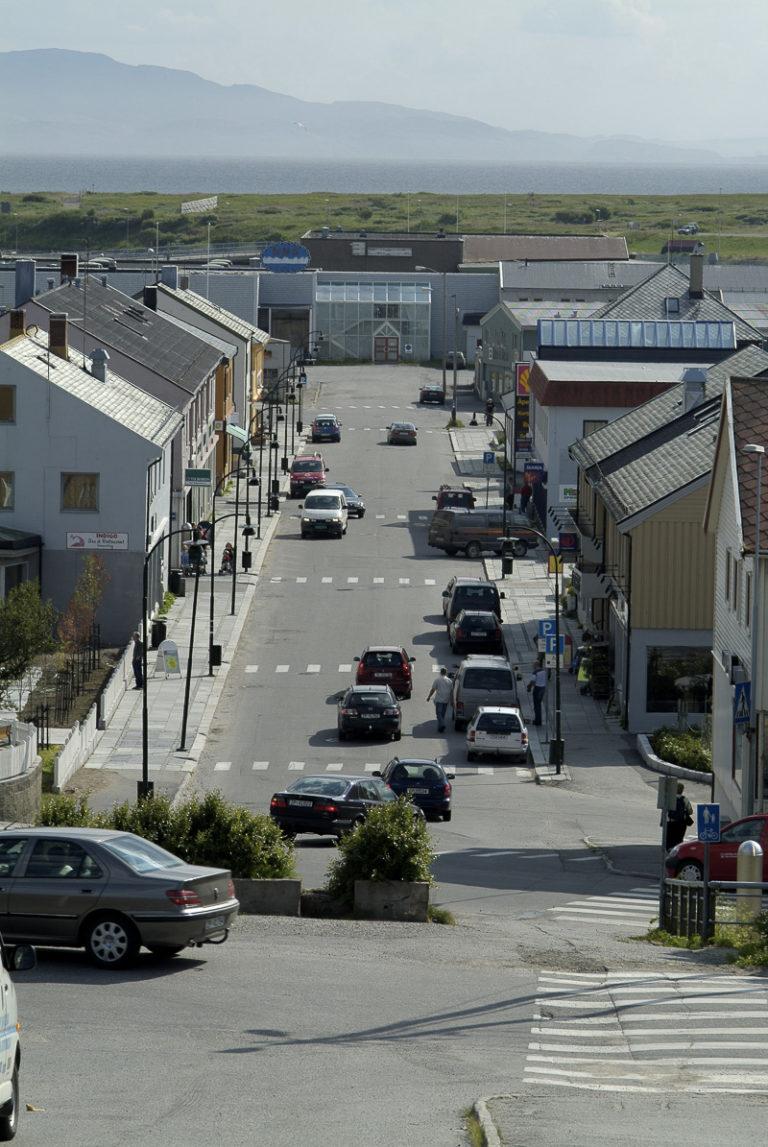 Hovedgata i Vadsø, sett fra kirkebakken, med forretningsgårder i gjenreisningsstil langs sidene. Kjøpesenteret i enden er nyere © Trym Ivar Bergsmo