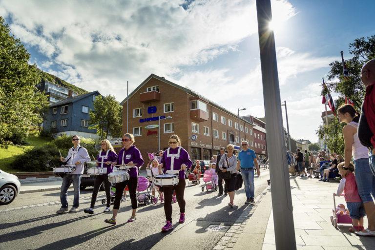 Festlig og fargerik gjenreisningsarkitektur i Hammerfest, med en forretningsgård foran og et typisk gjenreisningshus i blått over. Øverst ligger moderne leiligheter fra Hammerfests oljealder © Ziggi Wantuch