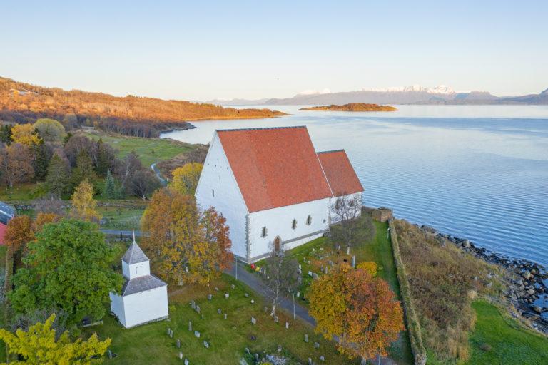 Trondenes kirke i høstskrud. Legg merke til restene av et tårn til høyre for koret i kirken © Jan Schmitt/ Visit Harstad
