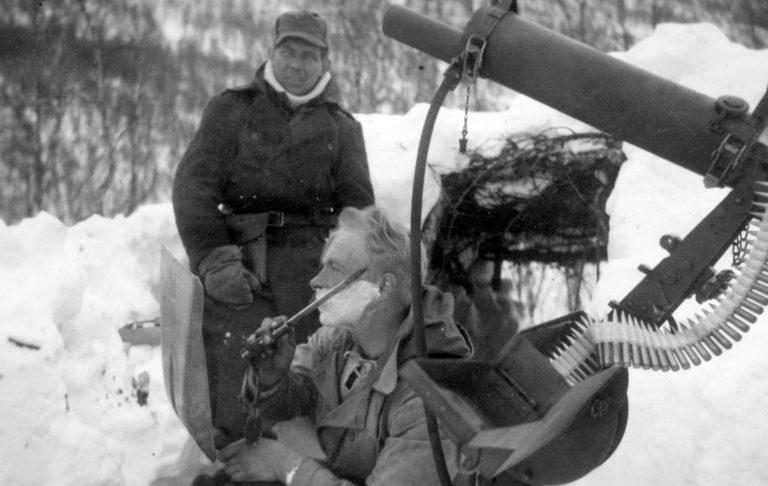 Fjellkrigen. Hygiene er viktig, også i felt. EN soldat fra IR15 trimmer skjegget ved en Colt mitraljøse.