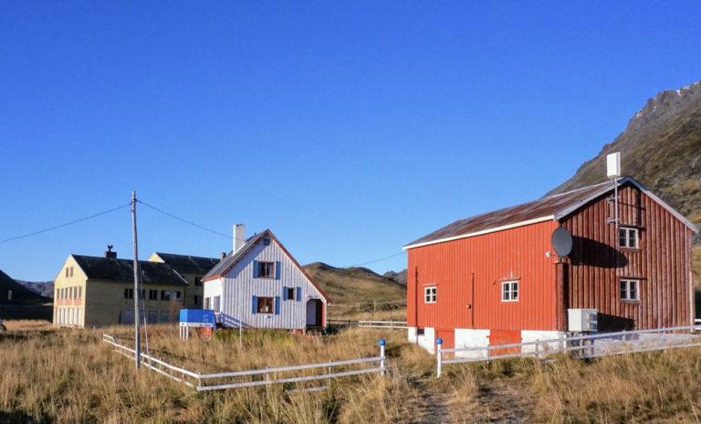 Gjenreisningsgård på Sarnes ved Honningsvåg, med et gjenreisningshus og en rødmalt låve. Like bortenfor ligger det gamle internatet fra 1958 © Knut Hansvold