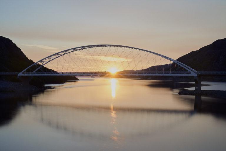 The bridge over River Pasvikelva between Kirkenes and the border. And the midnight sun © Emile Holba / www.visitvaranger.no