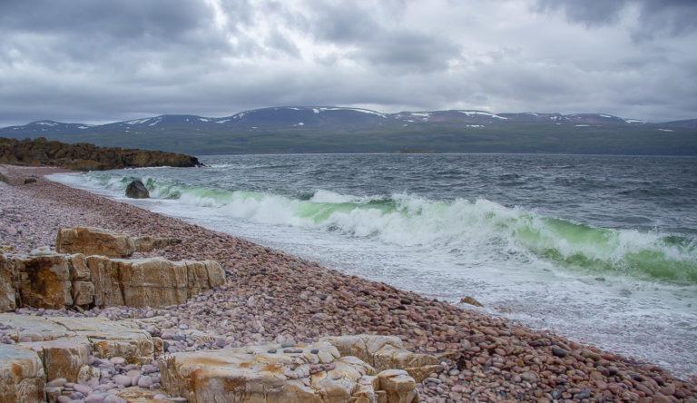 Grønne bølger slår mot den fargerike Luovttat-stranda ved Tanafjorden © Frank Martin Ingilæ