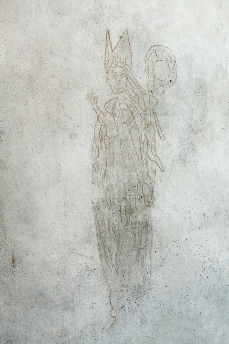 Denne biskopen er malt på kirkeveggen på 1400-tallet. Den gang hadde det sterke farger. Disse er gjenskapt på Trondenes historiske senter, men denne originalen har bleknet de siste 600 årene © Yvonne Holth/www.nordnorge.com