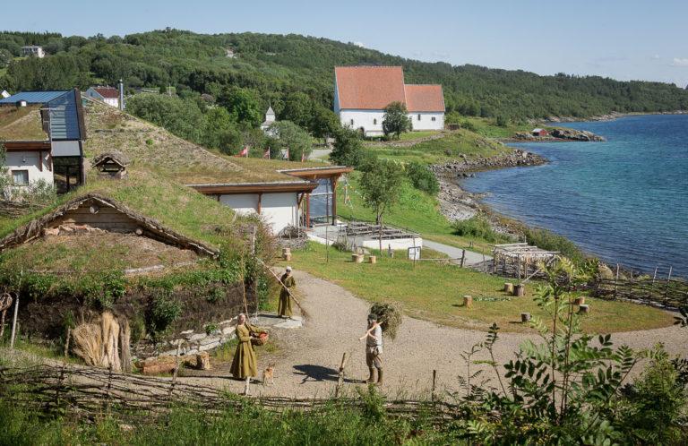 Utsikt fra tunet på Trondenes Middelaldergår forbi Trondenes Historiske Senter mot Trondenes kirke © Harriet M. Olsen/Sør-Troms museum